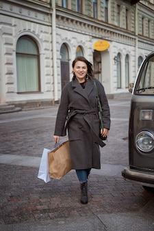 女性は彼女の手にバッグを持って通りを歩いて、成功した買い物を楽しんでいます