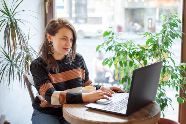 仕事に集中した。ウィンドウやカフェのそばに座っている間ラップトップに取り組んでスマートカジュアルな服装で自信を持って若い女性。