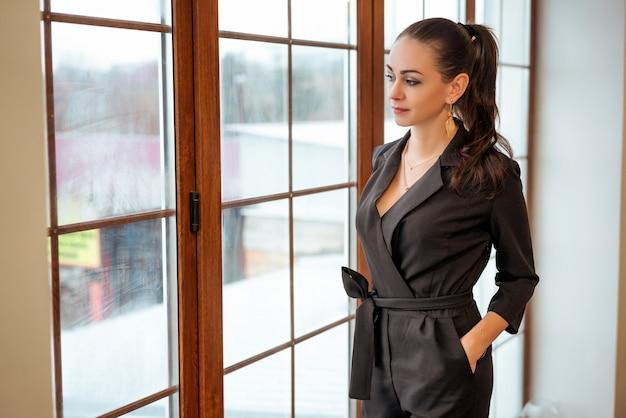 ファッショナブルな女の子が窓に立ちスタイリッシュな服に見えます