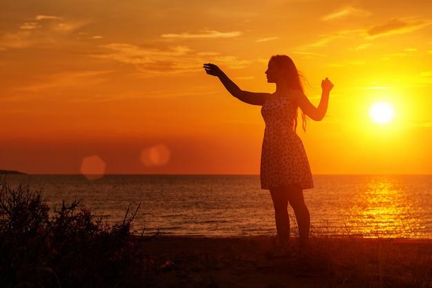 ビーチで夕暮れ時の女性のシルエット、手を挙げろ