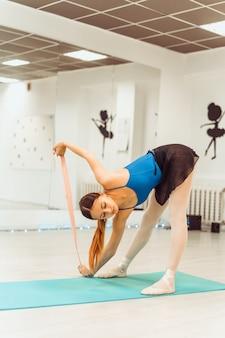 Женщина делает тренировки с резинкой в тренажерном зале