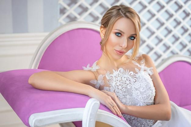 Портрет красивой женщины в белом свадебном платье с красивым макияжем и прической на диване