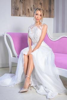 美しい結婚式のメイクアップとソファの上の髪を持つ女性の肖像画