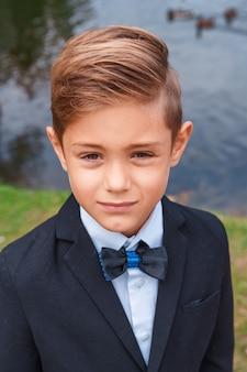 自然の中でスーツを着た少年の肖像画
