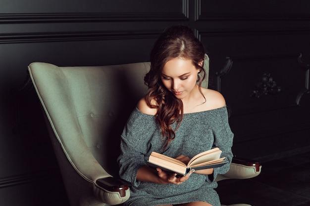 美しい女性の椅子に座って本を読む