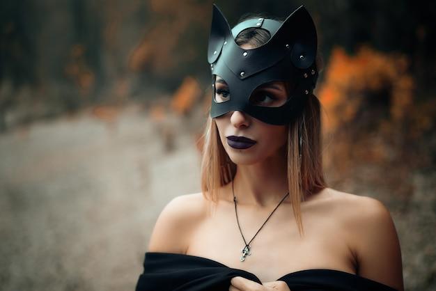 黒い猫のマスクを着た女性が自然の背景に立っています。