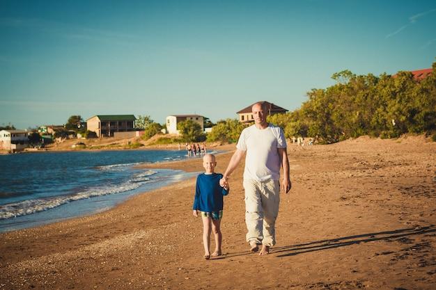 Счастливый отец и сын гуляя на пляж