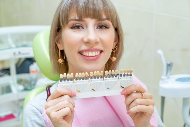 歯科、歯のホワイトニングで幸せな女の顧客