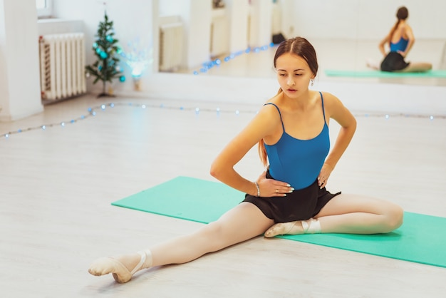 Девушка занимается гимнастикой, делает растяжку в тренажерном зале