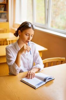 Симпатичная студентка сидит с ноутбуком за партой у окна, вдумчивый вид