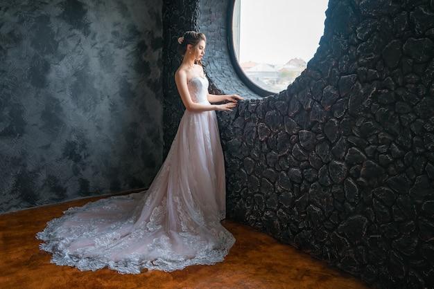 カメラにポーズをとって長いドレスの若い花嫁