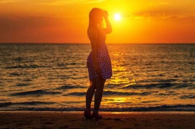 夕暮れ時のビーチのシルエット、夕方を歩く海岸