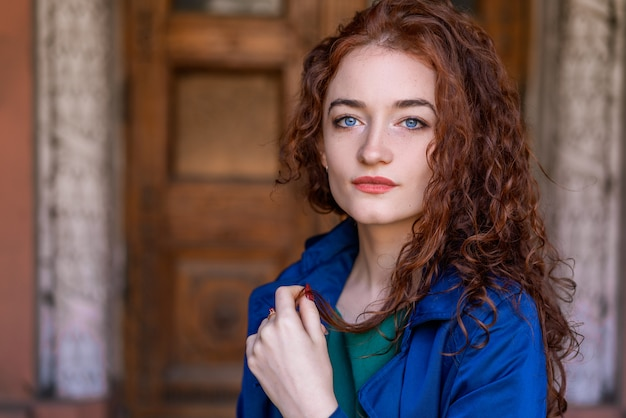 Портрет красивой женщины с рыжими волосами в синем плаще
