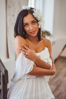 窓際に座っている白いドレスのセクシーなブルネット