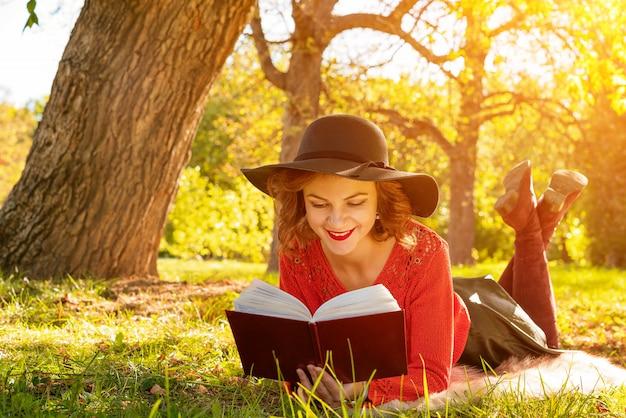 草の上に座って秋の公園で本を読んで素敵な女性