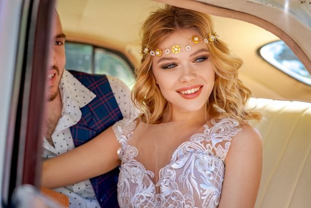 車のロマンチックな関係に座っている美しい若いカップル
