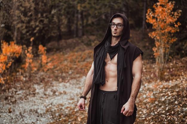 裸の胴体を持つ男が秋の森の上に立つ