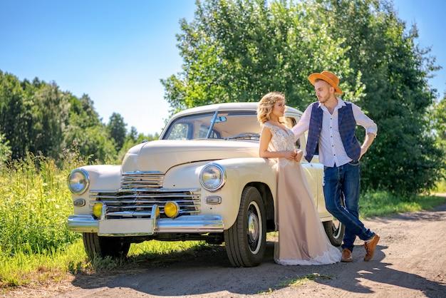 車のそばに立っている美しい若いカップル
