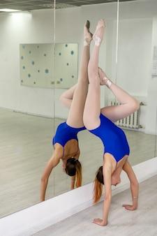 鏡で逆立ちをしている体操選手