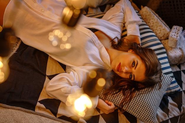 Красивая женщина в белой рубашке мужчины на кровати