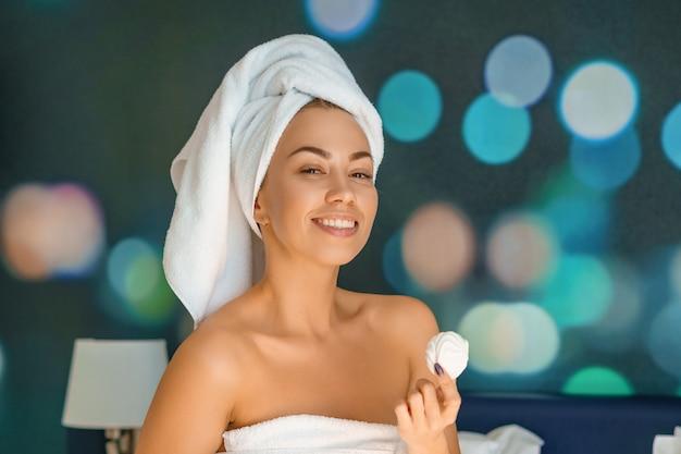 Сидеть красивой женщины усмехаясь в полотенце, концепции доброго утра