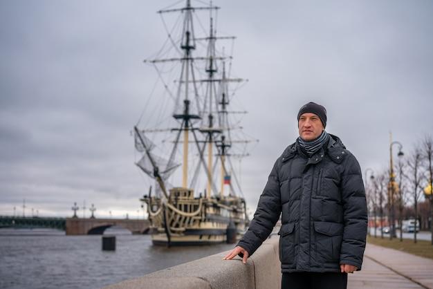 ネヴァ川の船に対してウォーターフロントに立っている男性