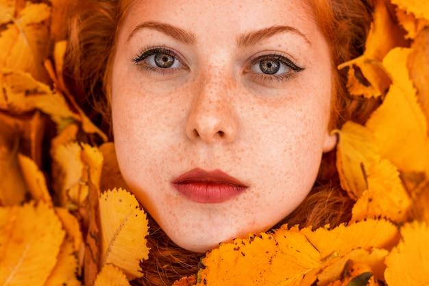 Красивый портрет крупным планом в желтых листьях, концепция осени