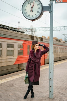 Гламурная женщина стоит на перроне железнодорожного вокзала и ждет поезда