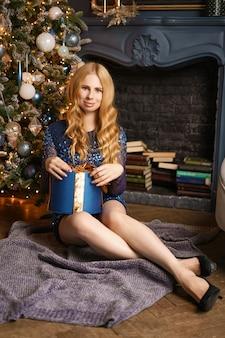 彼女の手に贈り物を持って座っている美しい若い女性のクリスマス気分。