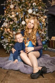 ママと息子のクリスマスツリー、休日の概念のポーズで座っています。