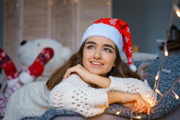 背景のボケ味のサンタクロースの帽子の美しい若い女性の肖像画