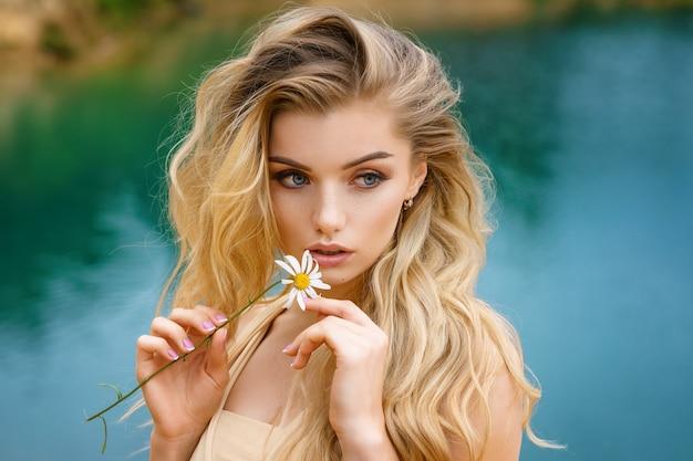 彼女の手、美しいメイクでデイジーと美しい少女の肖像画