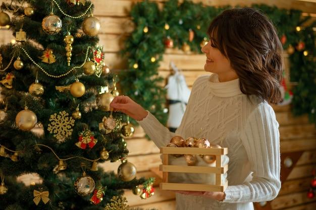 美しい幸せな女はクリスマスツリーをドレスアップ