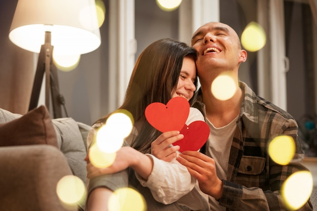 Счастливая пара, сидя на диване в объятиях красного сердца. размытые красивые боке. романтическая концепция.
