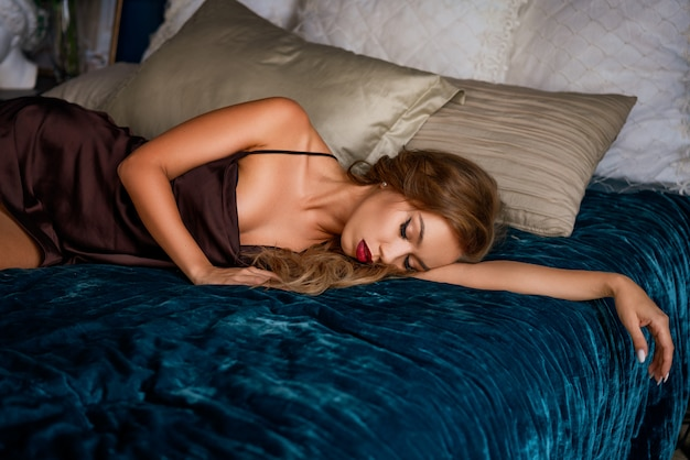 明るい化粧品で美しいセクシーな女性は、ベッドの上で彼女の下着に横たわっています。