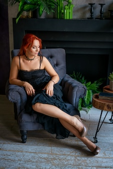 Красивая рыжеволосая женщина в черном платье сидит в кресле