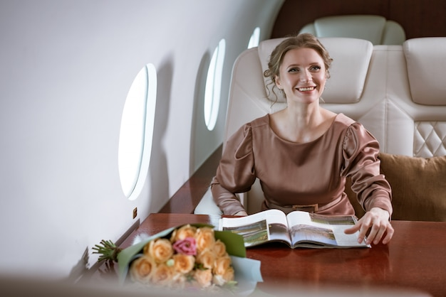 Счастливая стильная женщина сидит в частном самолете у окна