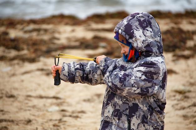 Мальчик в куртке на песке стреляет из рогатки