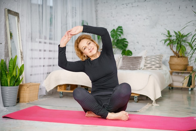 蓮華座に座って運動している年配の女性。自宅のリビングルームでストレッチ運動を行うアクティブな成熟した女性。