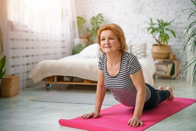 Старшая женщина тренируя домой, концепцию здорового образа жизни, фитнес и йогу