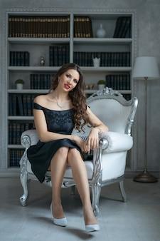 Красивая женщина с макияжем и красной помадой сидит в черном платье на белом стуле