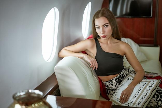 Красивая брюнетка женщина сидит в сиденье частного самолета