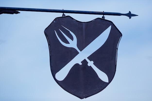 Железный знак кафе ножа и вилки пересекся с мрачным небом