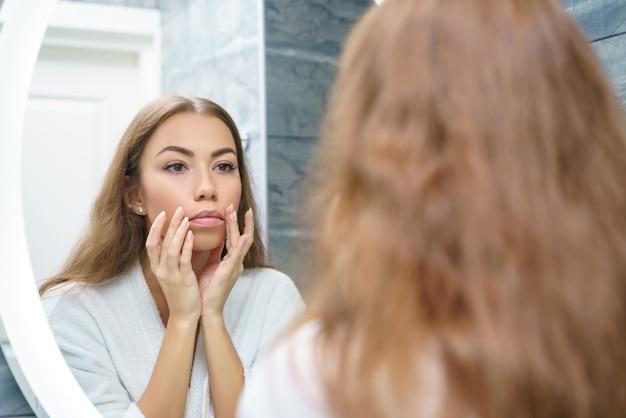 美しい若い女性は鏡で彼女の反射を見て、顔のマッサージを与える