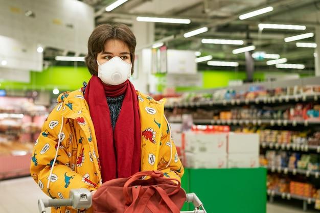 防護マスクの若い女性がスーパーでアルコールを選択し、在庫が隔離されます