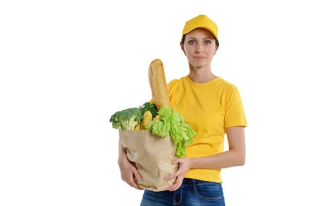 食料品の袋、白い背景で黄色のポーズでスマイリー配達の女性。