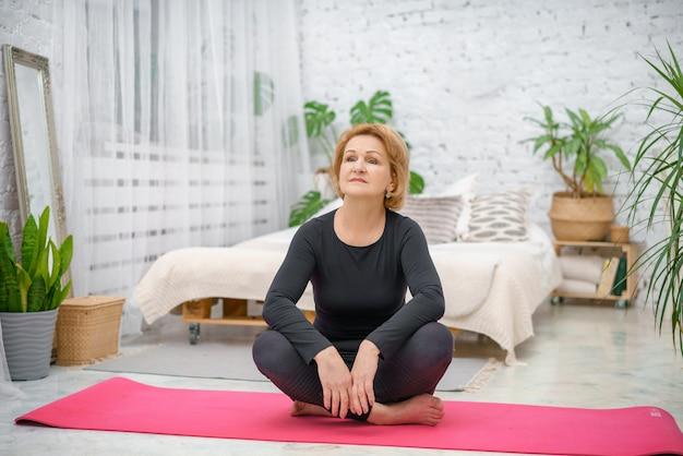 Зрелая женщина отдыхает на тренировочный мат после тренировки
