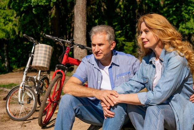 太陽の下で座っている自転車で湖のほとりに成熟したカップル