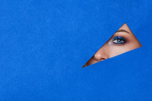Красивая молодая женщина в дыру в синей бумаге, красивый яркий макияж,