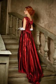 長い赤いレトロなドレスを着た美しい若い女性が階段に立っています。